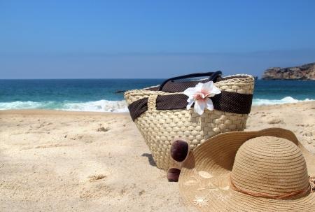 In mare - costa, occhiali da sole, borsa di paglia spiaggia e cappello