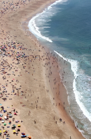 Sunny day in Nazare with a lot of people on the beach  photo