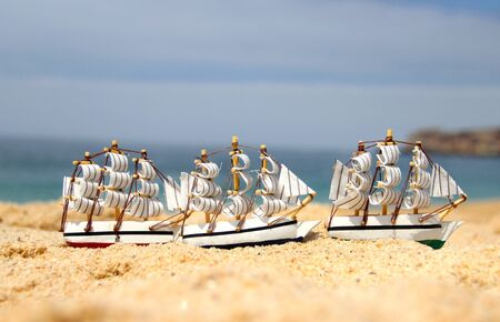 Sea composition: funny small toy sailing ships on the beach  photo