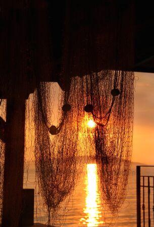 bounty: Relajación en la playa: puesta del sol maravillosa del mar con siluetas de palmeras y redes de pesca