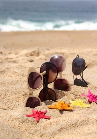 Familienurlaub vier Sonnenbrille am Strand und mehrfarbige Seesterne