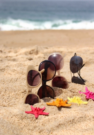 beach clothes: Family holiday four pair of sunglasses on the beach and multi color sea stars   Stock Photo