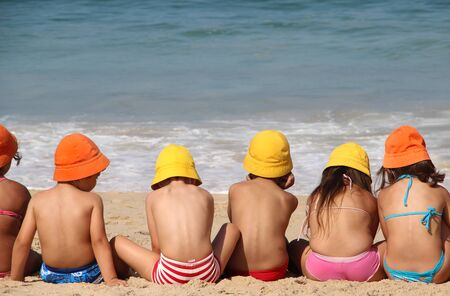 Cute children on the beach in vivid funny hats 