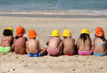 Funny children on the beach in the vivid swimming suits and funny multi coloured hats