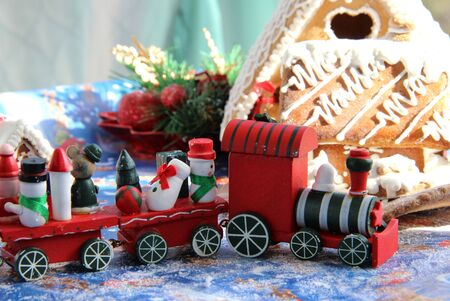 Christmas baked sweet houses and toy train with funny passengers    photo