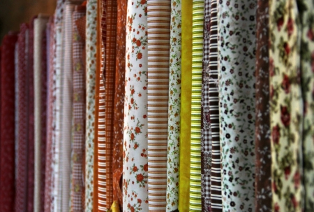 Big assortment of fabrics in the textile store  Stock Photo