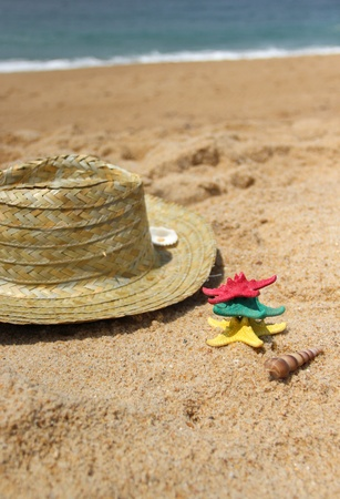Funny starfishes on the beach and straw hat photo