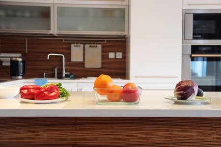 kitchenette: Well designed modern kitchen with a big variation of ripe fruit and vegetables on the table