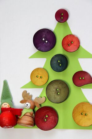 Paper Christmas tree decorated with vivid buttons and funny toys  photo