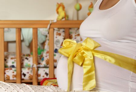 Pregnant woman tummy decorated with yellow ribbon and bow Stock Photo - 16953182
