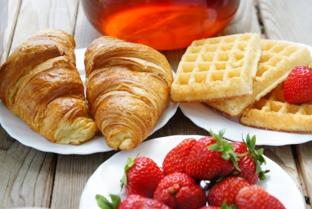 French breakfast - tea, croissants, wafers with cream and strawberries           photo