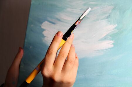 Artist's hand holding a paintbrush  photo