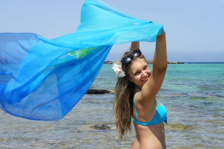 wind blown hair: Young happy woman on the beach with blue shawl          Stock Photo