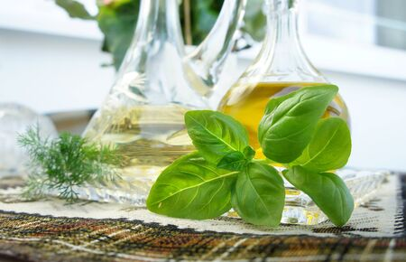 Olive oil, vinegar and basil in the beautiful crystal bottles   Stock Photo