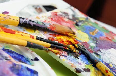 Beautiful vivid Art palette and mix of paintbrushes    photo