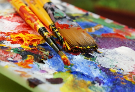 Beautiful vivid Art palette and mix of paintbrushes    Stock Photo