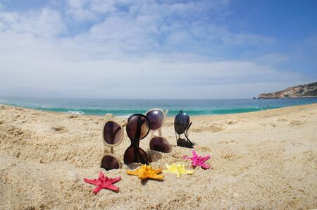 Holiday with friends – four pair of sunglasses on the beach and multi color sea stars