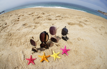 Holiday with friends – four pair of sunglasses on the beach and multi color sea stars   photo