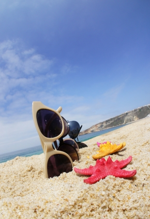 Holiday with friends – four pair of sunglasses on the beach and multicolor sea stars