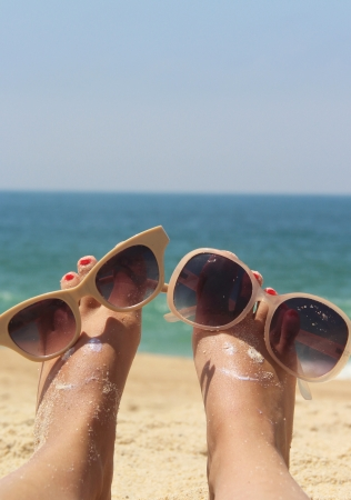 Summer holiday - funny female feet in sunglasses Stock Photo