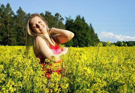 Young beautiful woman and field with beautiful yellow vivid flowers  photo