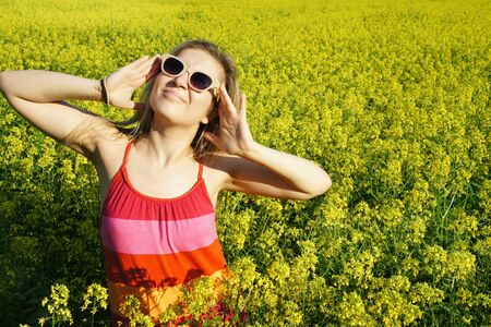 Young beautiful funny woman and field with beautiful yellow vivid flowers photo