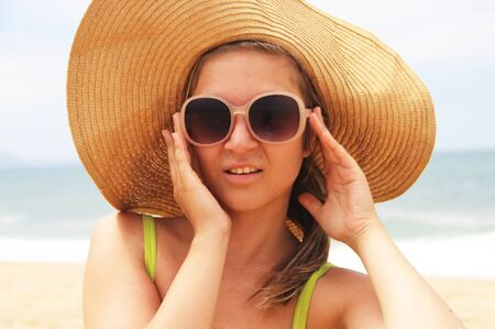 Young beautiful woman in straw hat on the beach photo