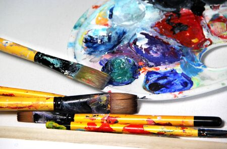Beautiful vivid art palette and mix of paintbrushes photo