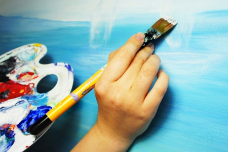 Artist�s hand with paintbrush painting the picture                  photo