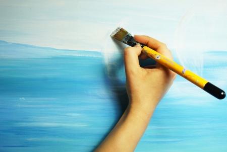 La mano del artista con pincel pintando la imagen