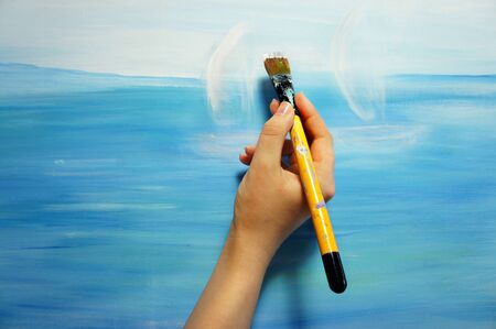 Artist's hand with paintbrush painting the picture   photo