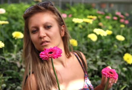 Beautiful woman in the greenhouse choosing the flowers photo