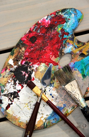 Big mix of paintbrushes and art palette at the artist workplace photo