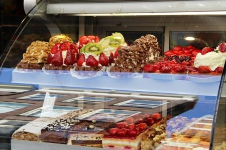 おいしいケーキやお菓子がたくさん店の窓 写真素材