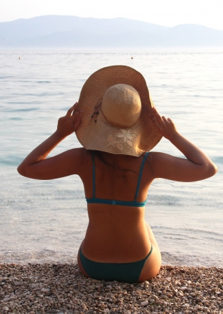 Young beautiful woman in straw hat sitting on the beach  photo