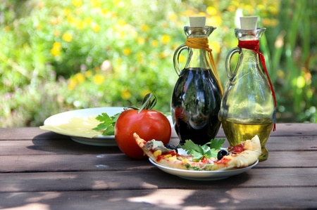 Piece of pizza in the summer garden table with olive oil and vinegar sauce