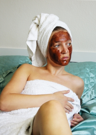 chocolate mask: Young beautiful woman applying chocolate mask on her face Stock Photo