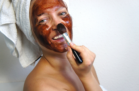 Young beautiful woman with chocolate mask on her face photo