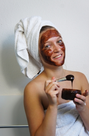 chocolate mask: Young beautiful woman applying chocolate mask on her face