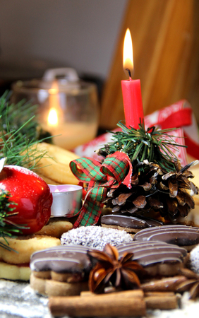 Mix of Christmas cookies with cinnamon, chocolate glaze and coconut with burning candle photo