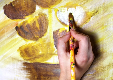 Artists hand with paintbrush painting the picture of beautiful flowers  photo