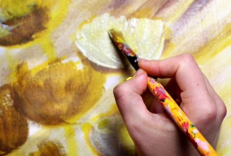 Artist hand with paintbrush painting the picture