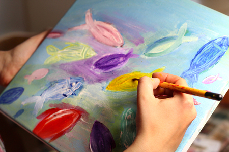 Artists hand with paintbrush painting vivid multicolored fishes in childish style photo