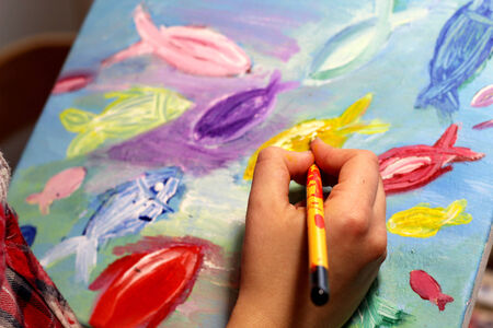 Artist�s hand with paintbrush painting vivid multicolored fishes in childish style photo