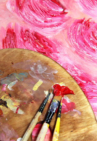 Paintbrush and beautiful painting of flowers in red and pink colors photo