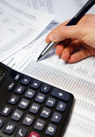 Taschenrechner, Stift und Buchhaltungsbeleg mit einer Menge von Zahlen und Frau Hand
