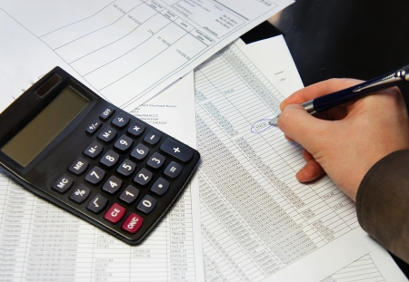 Calculator, pen and accounting document with a lot of numbers  photo