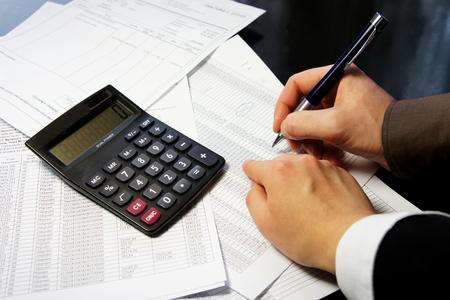 電卓、ペン、および多くの数字と男と女の手で会計伝票 写真素材