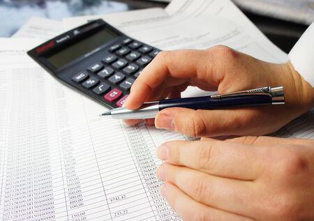 電卓、ペン、および多くの数字と女性の手で会計伝票 写真素材