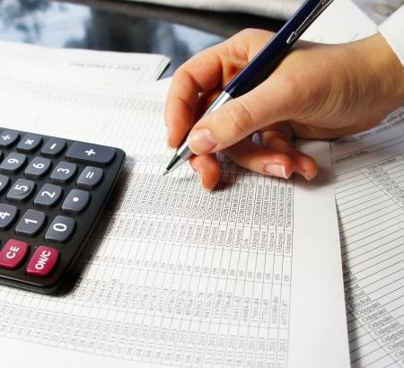 Taschenrechner, Stift und Buchhaltungsbeleg mit einer Menge von Zahlen und Frau, die Hände